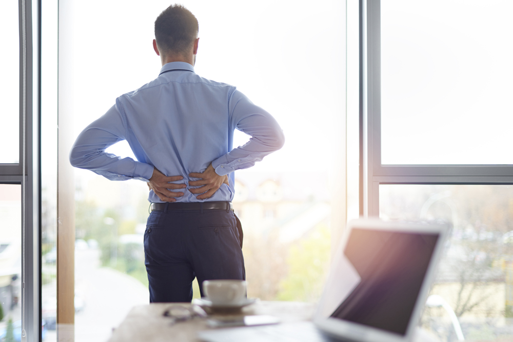Man suffering from back pain at work